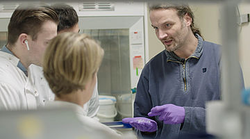 Professor Kristian Franze in his laboratory with students.